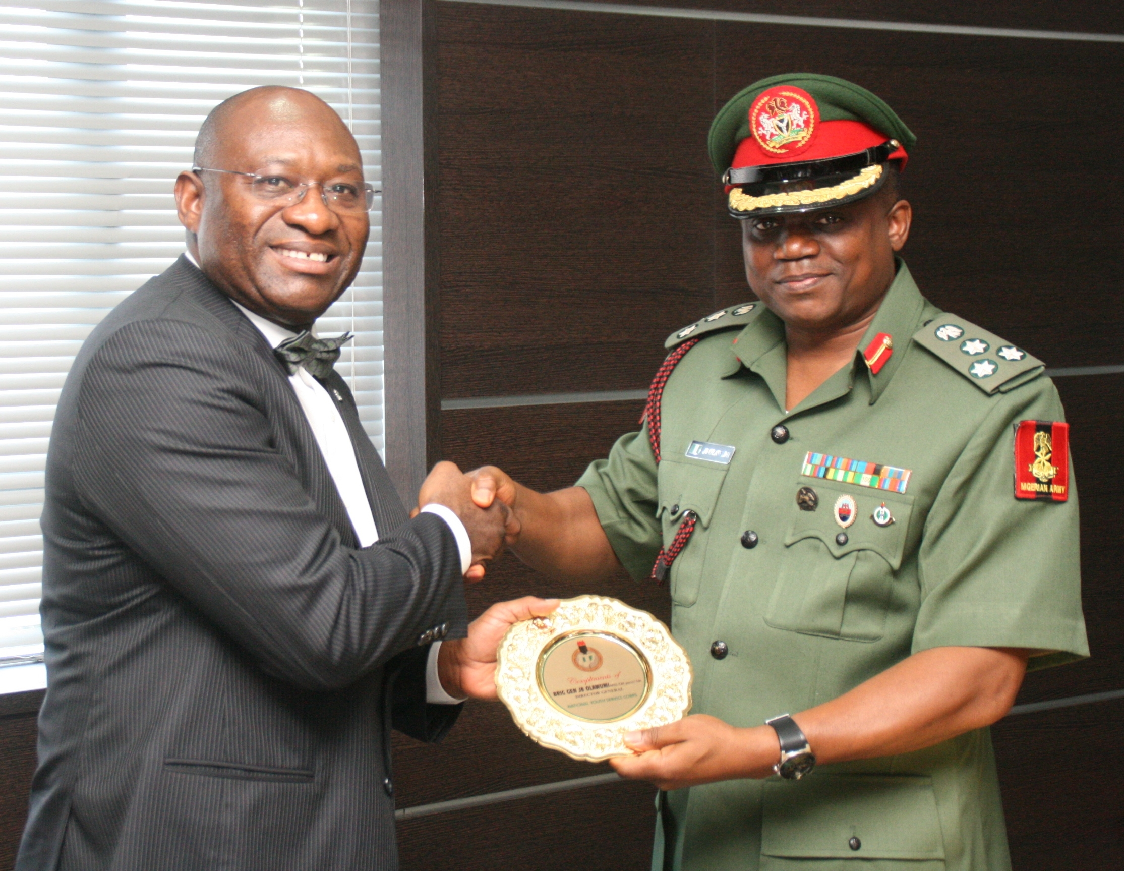 (L-R): Managing Director, Heritage Banking Company Limited, Mr. Ifie Sekibo receiving a commendation award plaque from the Director-General, National Youth Service Corps, Brigadier General Johnson Olawunmi during a courtesy visit by the NYSC Management team to the Bank's head-office on Tuesday